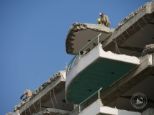 Workers using jackhammers at the top of a seven storey building