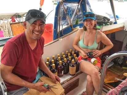 Dominic and Sabrina wrapping the rum bottles in foam so they can be stored without clinking on the boat